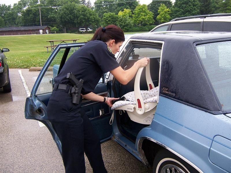 Police Officer Placing Baby Carrier in Car
