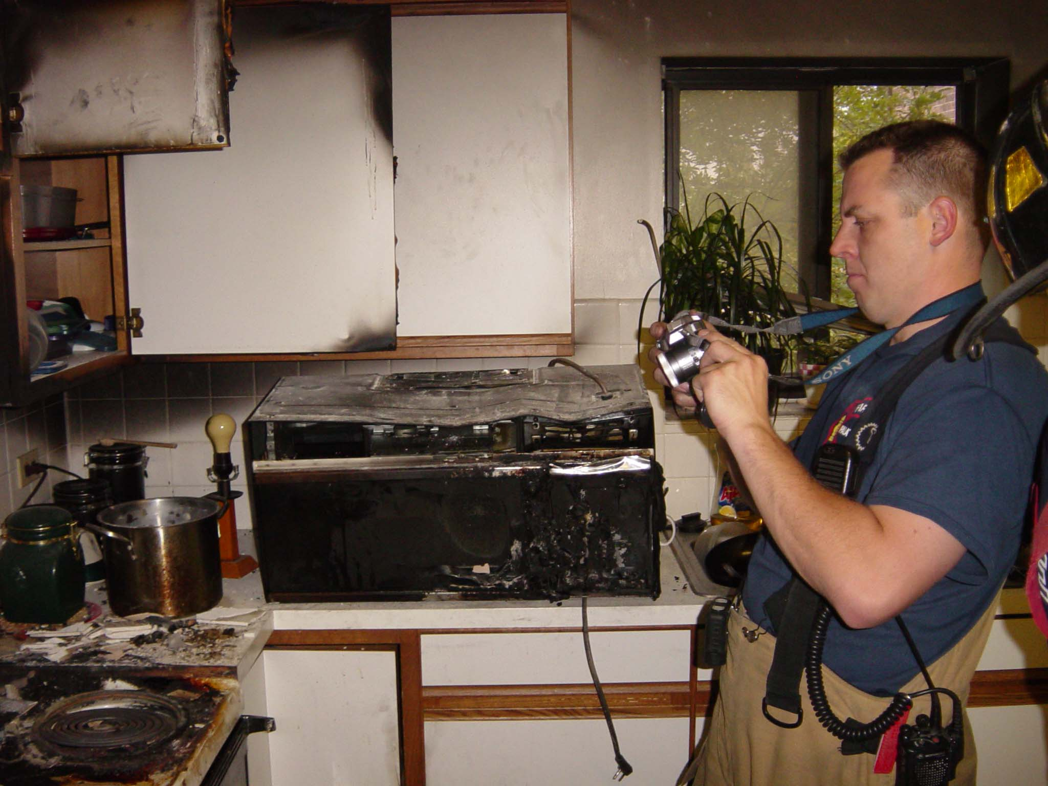 Investigator taking photos at a fire scene.